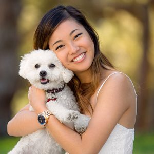 Smiling woman holding her puppy